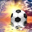 图库照片: Soccer ball reflected in water over blue sky with sunset
