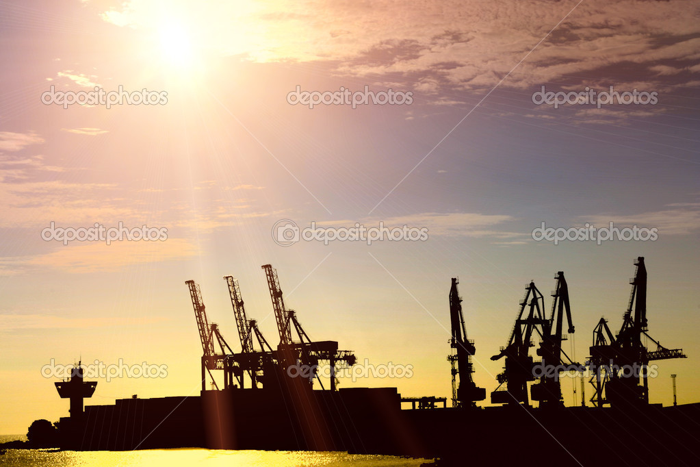 Silhouette of portal cranes in harbor on sunset — Stock Photo #12981035