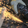 Worker cutting metal with many sharp sparks — Stock Photo #13148462