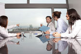 Four businesspeople looking out of the window — Stock Photo