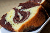 Slices of homemade marble cake on a white plate with brown backround — Stock Photo