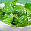 Raw spinach leaves in a white bowl with green  background — Stock Photo