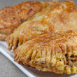 Pasties filled with minced meat on a white plate with beige background — Stock Photo