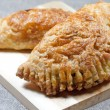 Pasties filled with minced meat on a wooden board with beige background — Stock Photo