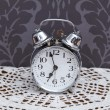 Antique alarm clock on table cloth — ストック写真