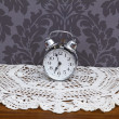Antique alarm clock on table cloth — Stock fotografie #18325245