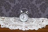 Antique alarm clock on table cloth — Stock Photo