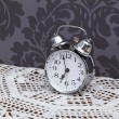 Antique alarm clock on table cloth — Stockfoto