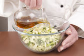 Female chef fills some oil into a salad — Stock Photo