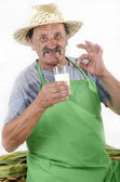 Organic farmer is holding a glass of milk — Stock Photo
