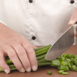 Female chef cuts spring onion with a large knife — Stock Photo