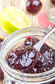 Home made cherry jam in a glass with a spoon — Stock Photo
