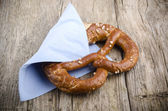 Salty pretzel with a blue napkin — Stock Photo