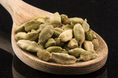Whole cardamom on a kitchen spoon — Stok fotoğraf