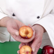 Female chef holds a cut through plum — Stock Photo