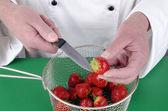 Female chef preparing some strawberries — Stock Photo