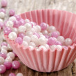 Mini pink cupcake case with pearls — Stock Photo