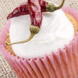 Cupcake with icing and red chili - Stock Photo