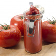 Tomatoes and tomato paste in a glass — Stock Photo #25448527