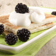 Potato pancakes with sour cream and blackberries — Stock Photo