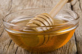 Honey and dripper in a small glass bowl — Stock Photo