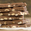 Broken milk chocolate with hazelnuts — Stock Photo