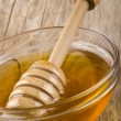 Honey and a dipper in a small bowl — Stock Photo