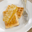 Waffle with honey on a plate — Stock Photo