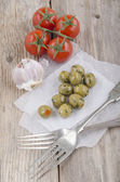 Green stuffed spicy olive on white paper — Stock Photo