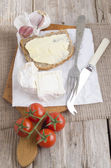 Goat cheese and bread on a wooden board — Stock Photo