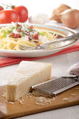 Parmesan cheese and grater on wood — Стоковое фото