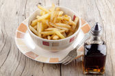 French fries and malt vinegar — Stock Photo