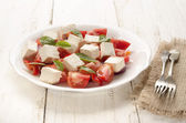 Salat with tomato and goat cheese — Stock Photo