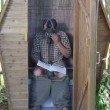 Male sitting in a summer toilet with Gas Mask on — Stock Video