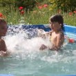 Stock Video: Kids have fun swimming in a pool with nice blue water