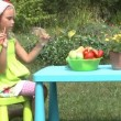 Little girl eats a carrot outdoors  — Stock Video