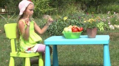 Little girl eats a carrot outdoors — Stock Video