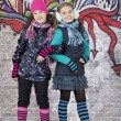 Girls in front of the wall covered with graffiti — Stock Photo