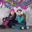 Two girls in front of the wall covered with graffiti — Stock Photo