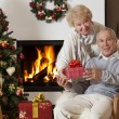 Senior couple exchanging Christmas gifts — Stockfoto