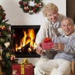 couple de personnes âgées échangeant des cadeaux de Noël — Photo