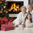 Senior couple with granddaughter enjoying Christmas — Stockfoto
