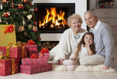 Senior couple with granddaughter enjoying Christmas — Stock Photo