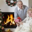 Happy senior woman getting Christmas present — Stock Photo