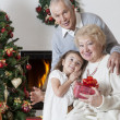Senior couple with granddaughter celebrating Christmas — Stock Photo