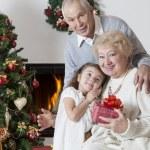 Senior couple with granddaughter celebrating Christmas — Stock Photo