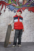 Skater boy in front of wall — Stock Photo