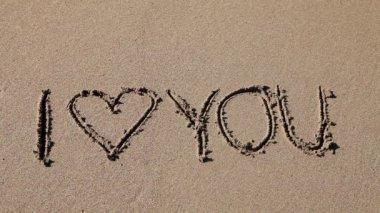Jag älskar dig skriftligt i sanden — Stockvideo