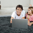 Couple With Laptop On Rug — Stock Photo #12438455