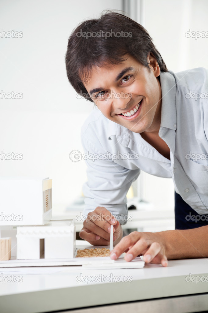 Portrait of young male architect smiling while creating a model house — Stock Photo #12438351